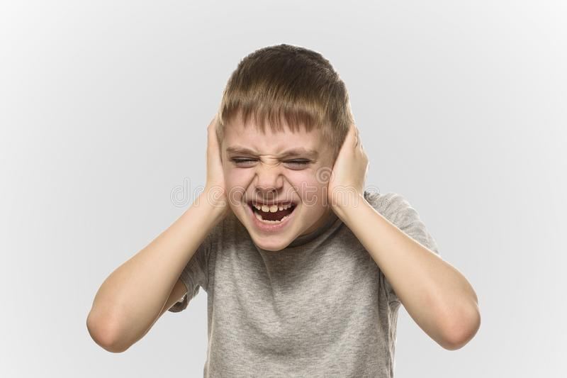 Boy closed his ears with his hands and shouts furiously. Naughty schoolboy. Isolate.  royalty free stock photography