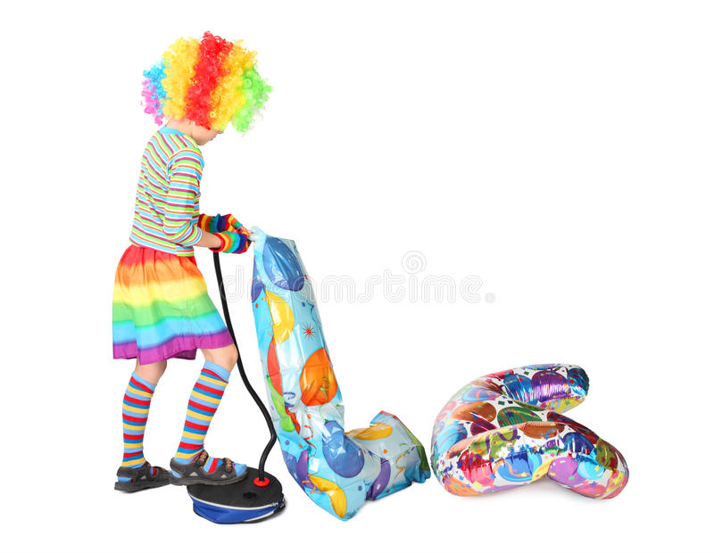 Boy in clown dress pupming birthday balloons royalty free stock photos