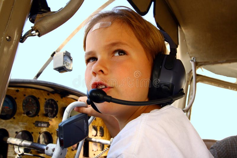 Boy in cockpit of private airplane. A little boy, age 6, sits in the cockpit of a private aircraft, Cessna 172, with headset on. He is pretending to be talking royalty free stock photo
