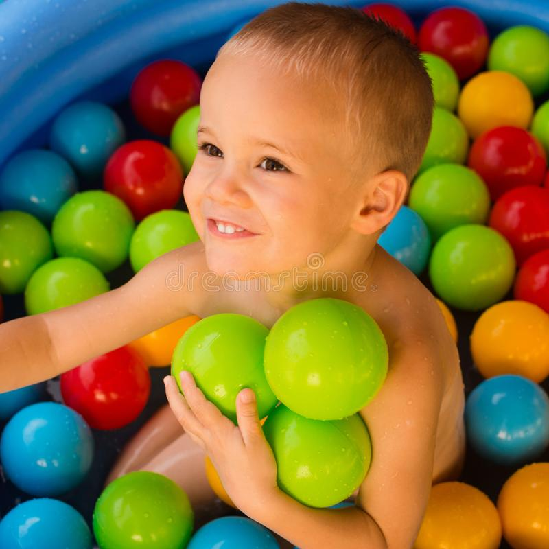 Boy with colorful balls in pool stock photography