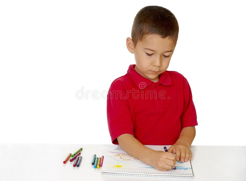 Boy coloring with crayons. Seven-year-old boy coloring with generic crayons stock images
