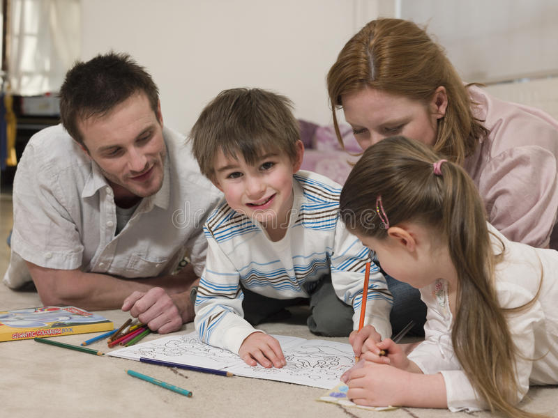 Boy Coloring Pictures While Family Looking At It On Floor royalty free stock images