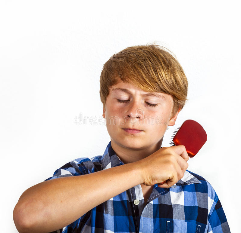 Boy combs his hair. Boy combs his bonde hair with a red hairbrush royalty free stock images
