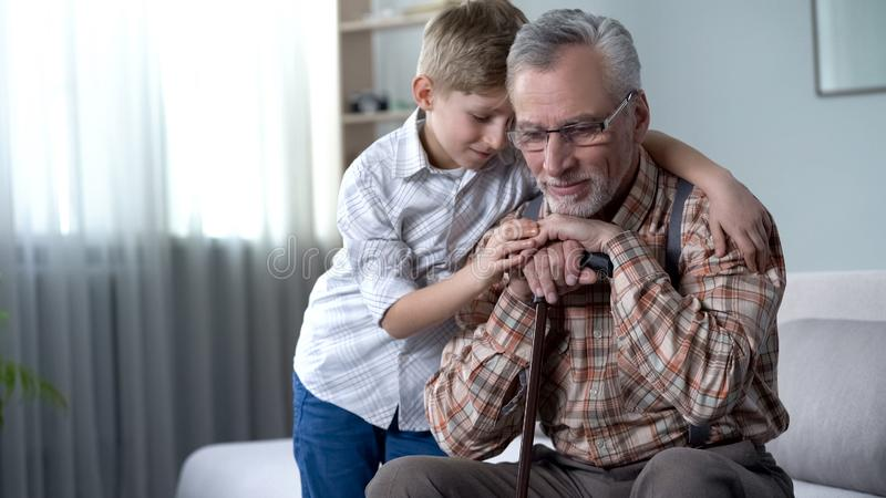 Boy comforting old lonely man, embracing him, charity program in nursing home royalty free stock photo