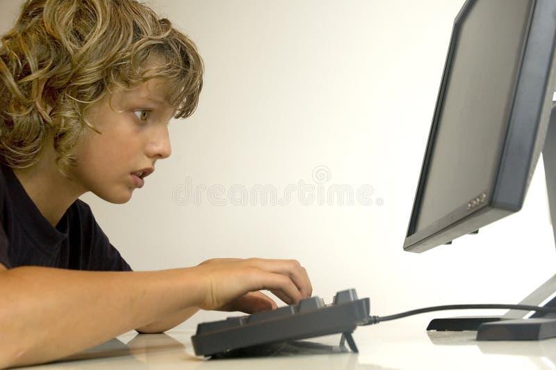 Boy at computer stock photos