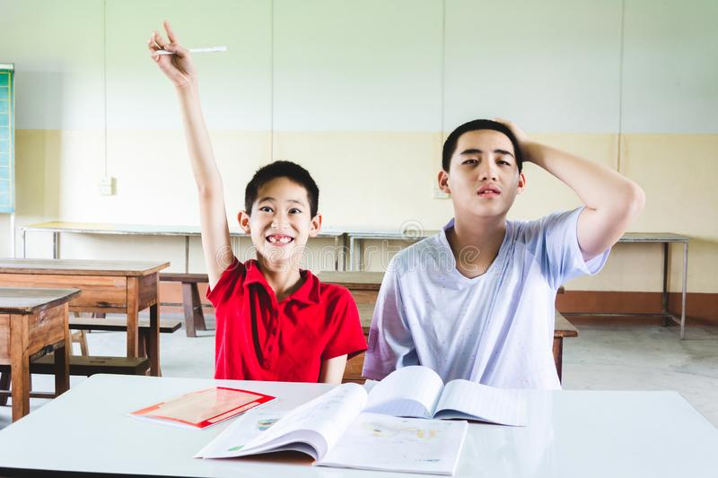Boy confused with answer but another one hand raise up to answer the question stock images