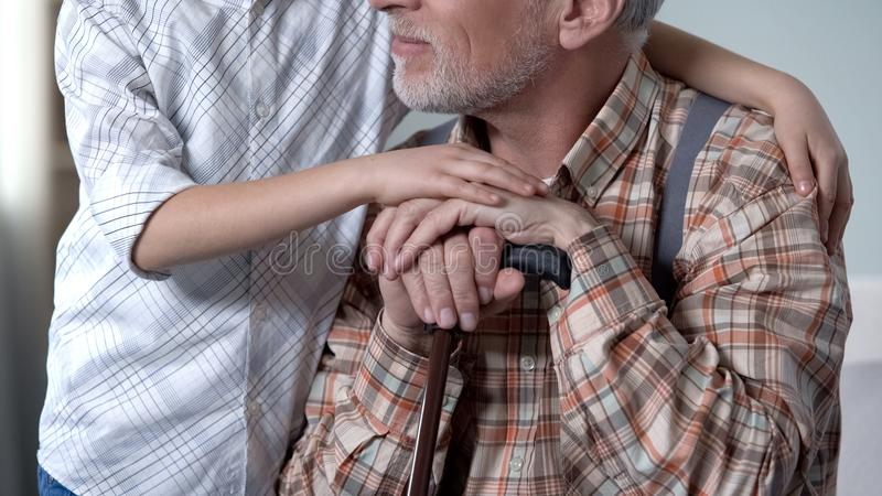 Boy consoling old lonely man, embracing him, charity program in nursing home stock images