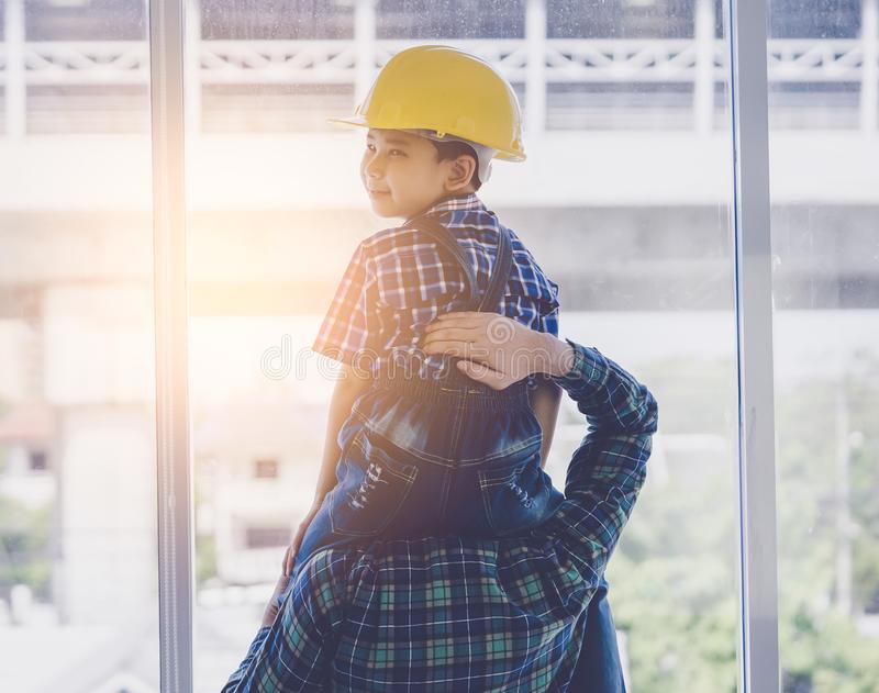 Boy in construction helmet sitting on father neck looking back with sunlight for father and son builder future concept stock images