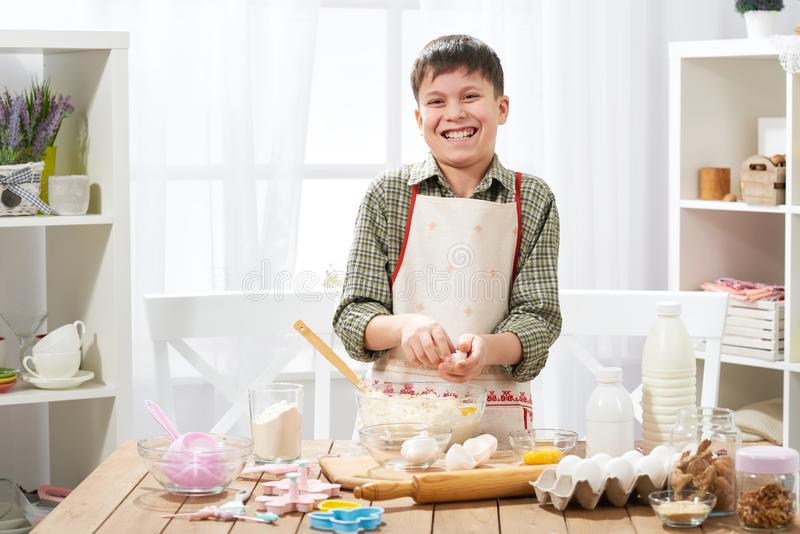 Boy cooking at home, making dough, buns and cookies royalty free stock photography
