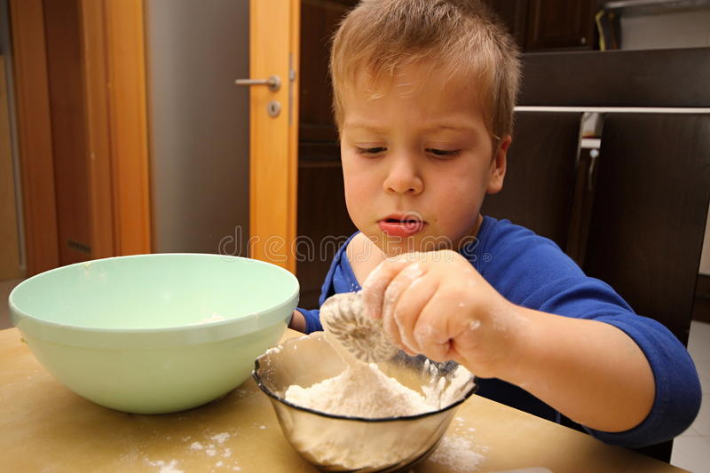 Boy cooking sweets with flour and saucer holding shape. Boy cooking sweets with flour and saucer holding metal shape royalty free stock photography