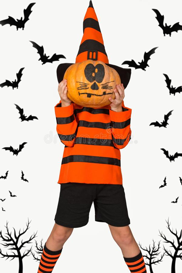 Halloween.Boy in a costume wizard a pumpkin on his head.Decor for Halloween. royalty free stock image