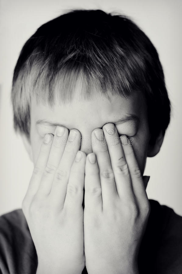 Boy Covering Eyes with Hands stock images
