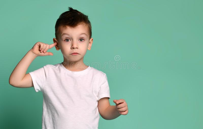Boy covering his ears over green background. stock images