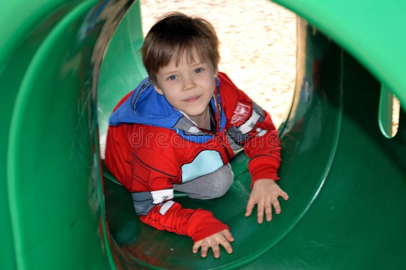 Download Boy Crawling Through A Playground Tunnel Stock Photo - Image of veterans, play: 107917554