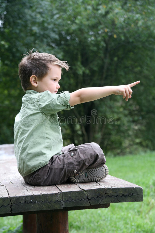 Boy cross-legged on a wooden bench stock images