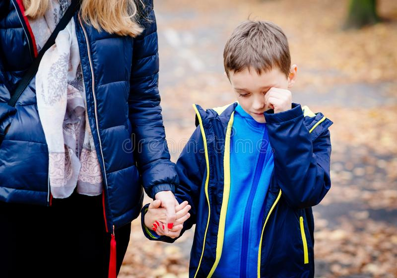 Boy crying and holding his mother hand during the walk stock photo