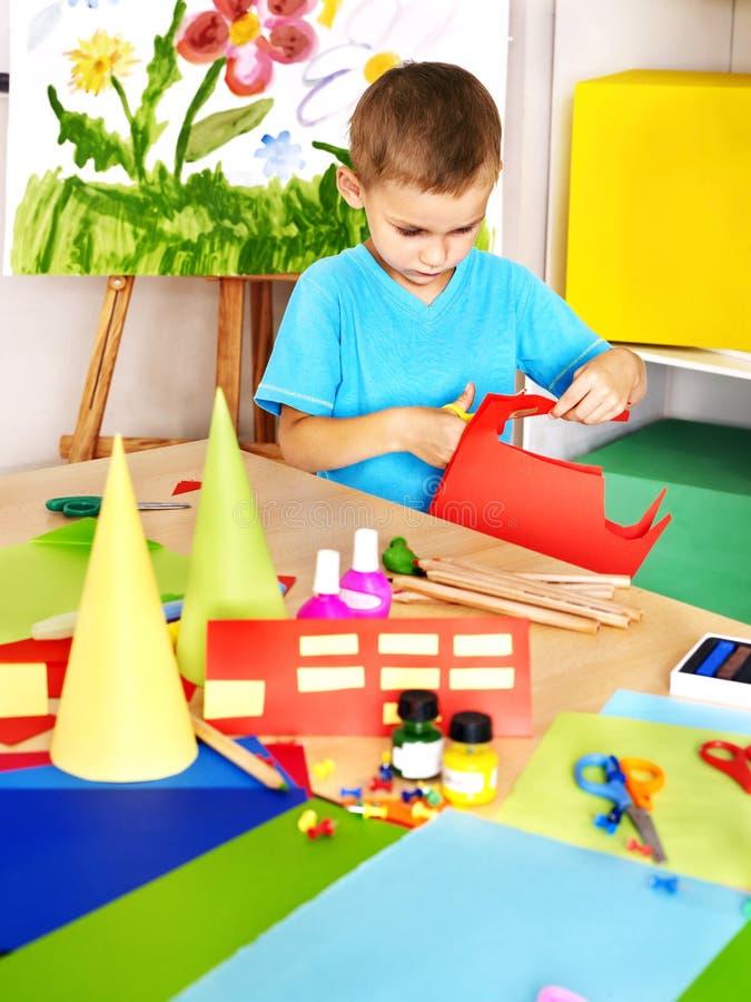 Boy cut paper in preschool. Boy cut paper by scissors in school royalty free stock image