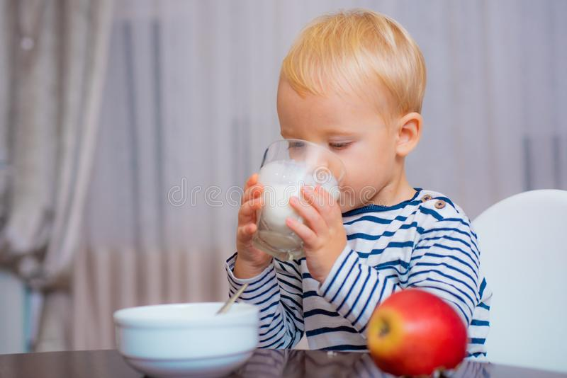Boy cute baby eating breakfast. Baby nutrition. Eat healthy. Toddler having snack. Healthy nutrition. Drink milk. Child stock photography