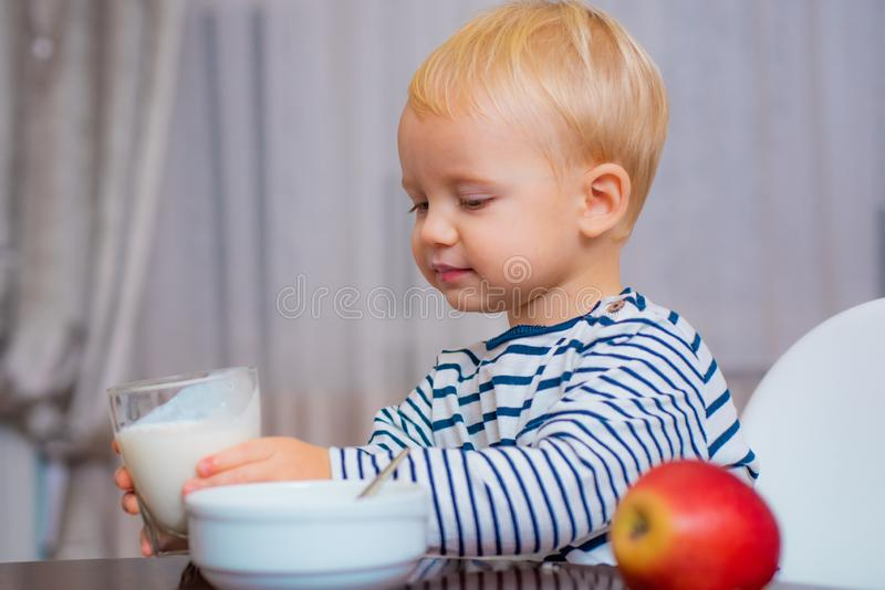 Boy cute baby eating breakfast. Baby nutrition. Eat healthy. Toddler having snack. Drink milk. Child hold glass of milk royalty free stock photo