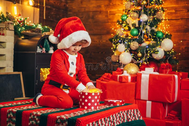 Boy cute child cheerful mood play near christmas tree. Merry and bright christmas. Lovely baby enjoy christmas royalty free stock image
