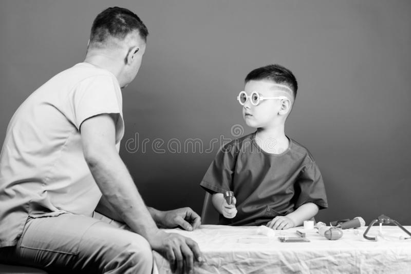 Boy cute child and his father doctor. Hospital worker. Health care. Medicine concept. Kid little doctor sit table royalty free stock photo