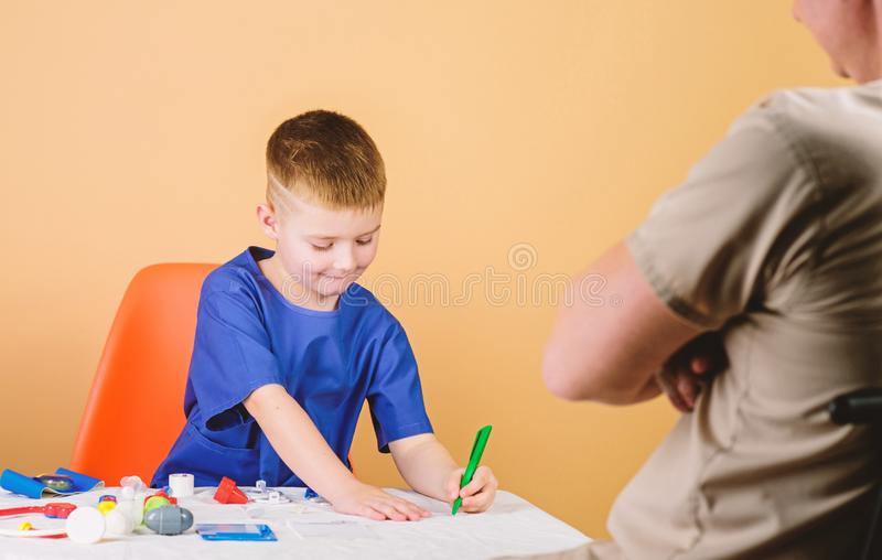Boy cute child and his father doctor. Medical examination. Child care kindergarten. Hospital worker. Medical service. Kid little doctor sit table medical tools royalty free stock photos