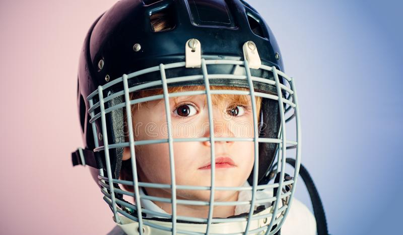 Boy cute child wear hockey helmet close up. Safety and protection. Protective grid on face. Sport equipment. Hockey or. Rugby helmet. Sport childhood. Future royalty free stock photos