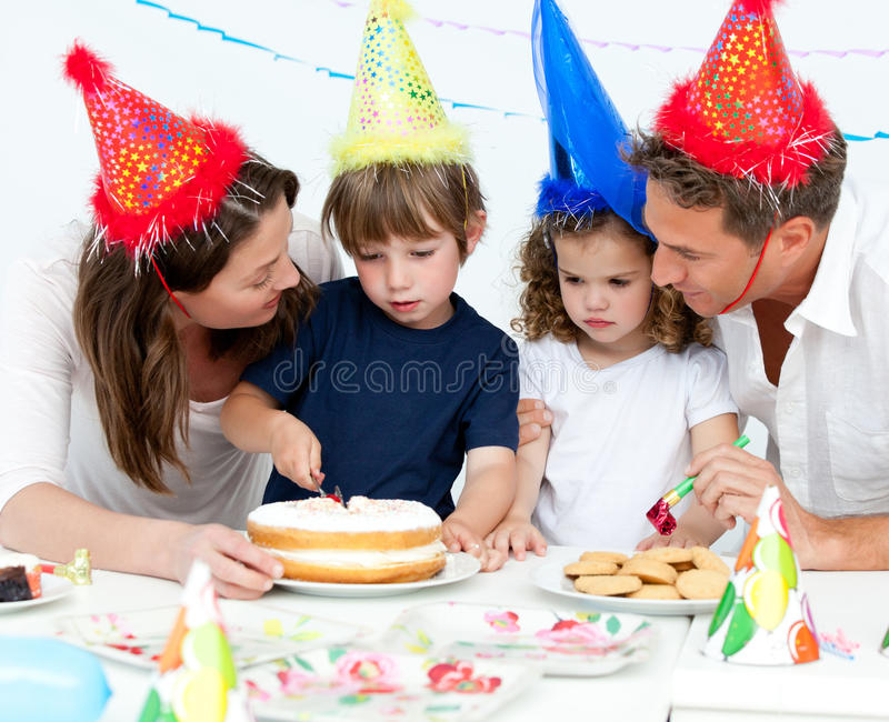 Boy cutting a birthday cake for his family. Cute little boy cutting a birthday cake for his family in the kitchen stock images