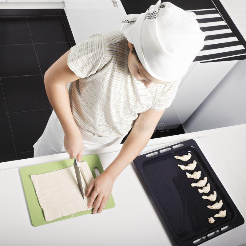 Boy cutting dough stock photos