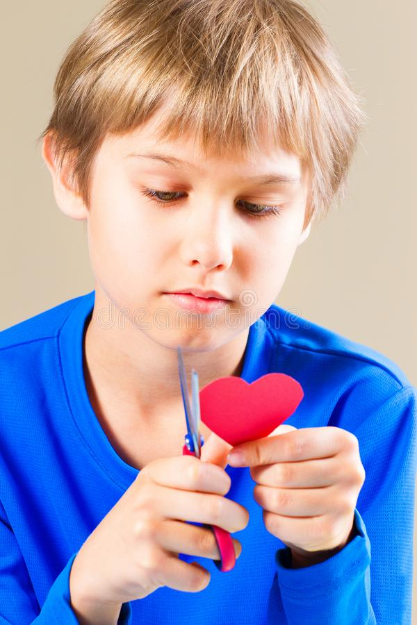 Boy cutting red paper heart with scissors stock images