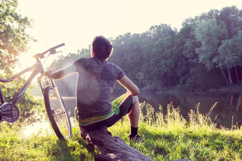 Boy cyclist sits and looks afar near the river stock photos