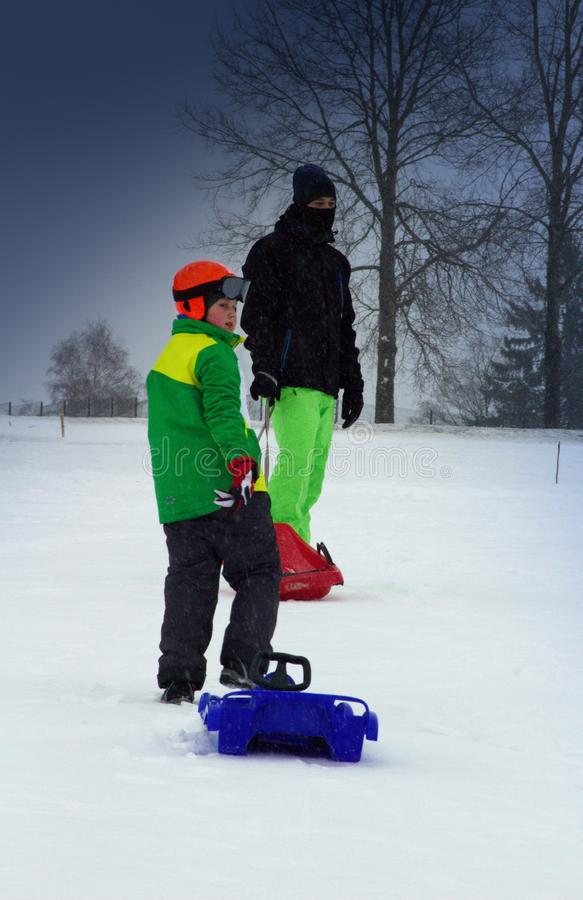 Boy and his dad ride on plastic bobs in winter. The boy and dad are about to ride on bobs stock photos