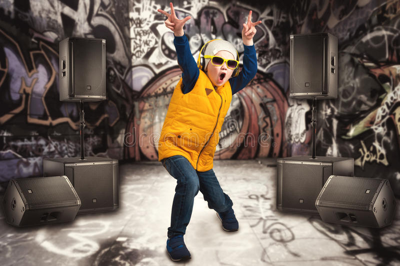 Boy dancing Hip-Hop . Children`s fashion.The Young Rapper.Graffiti on the walls.Cool rap DJ. Children`s fashion.The Young Rapper.Graffiti on the walls.Cool rap stock photos