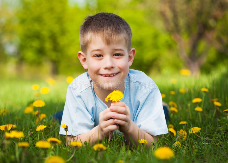 Boy with dandelions in a green park. summer