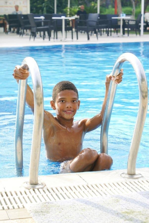 Boy dans la piscine photo stock