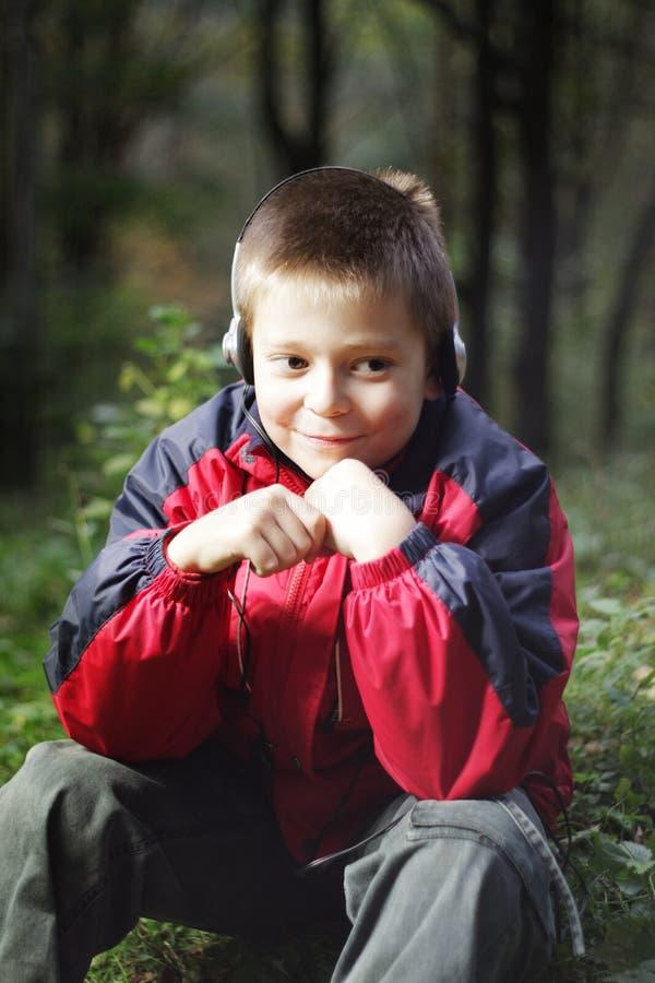 Boy in dark forest listens music
