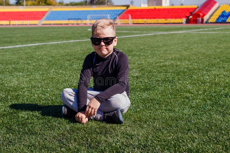 Boy in dark glasses sitting on the grass at the sports stadium stock image