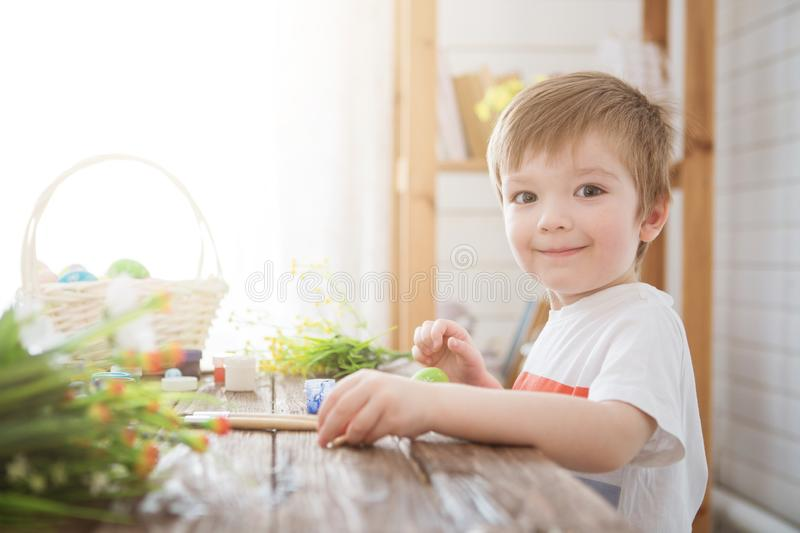 Boy decorate easter egg. A little boy painting and decorating Easter eggs. Portrait of cute boy 3 years old. He holds brush and royalty free stock photo