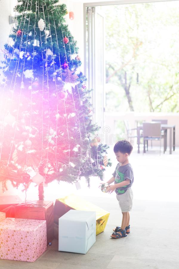 a boy is decorating a Christmas tree with present and mirror balls. royalty free stock photos