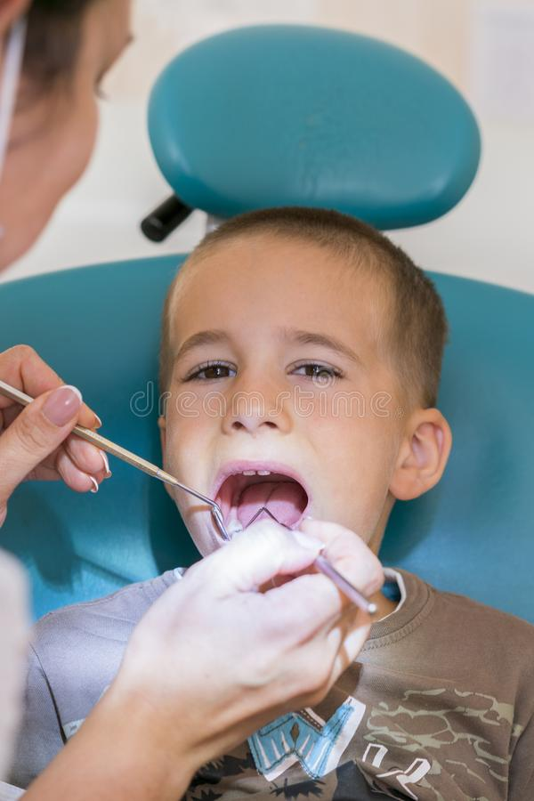 The boy at the dentist. A dentist examines the teeth of a small boy. vertical photo.  royalty free stock images