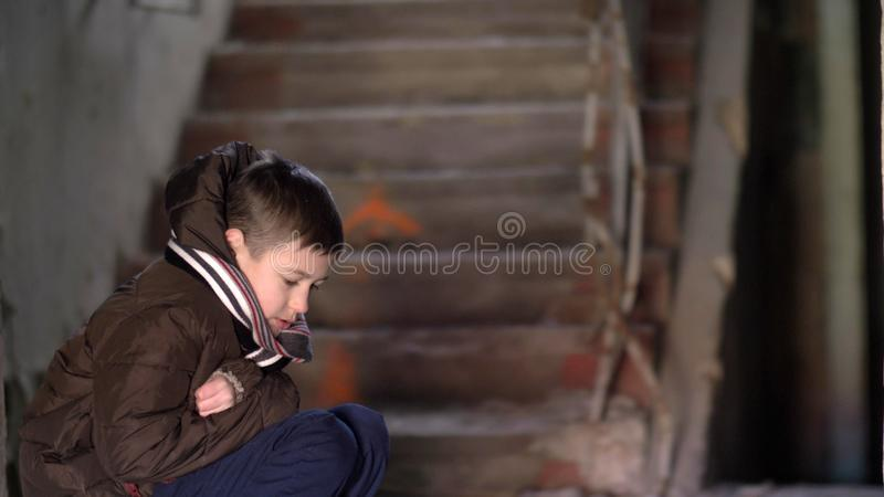 Boy in depression, hiding from the cold in an old dilapidated house royalty free stock photography