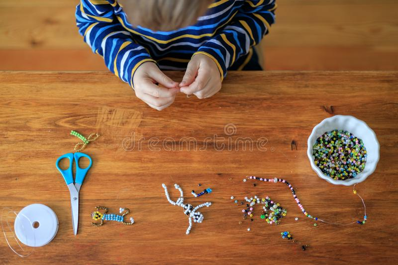 Boy is designing toys from multicolored beads at home stock image
