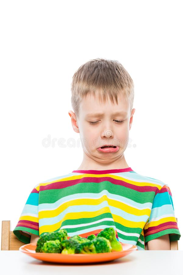 Boy with disgust looks at a plate of broccoli, portrait on white background stock images