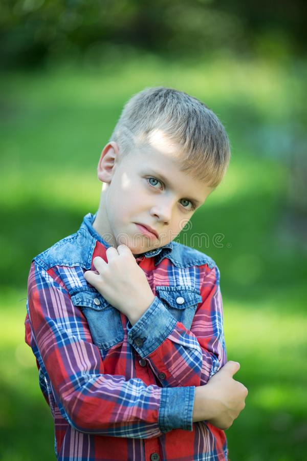 Boy with a displeased facial expression. In the garden royalty free stock photos