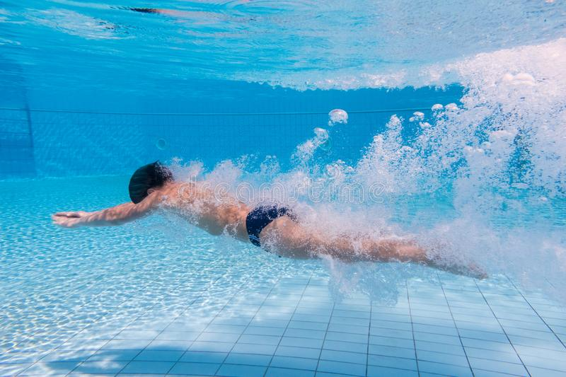 Boy dive in swimming pool royalty free stock photo