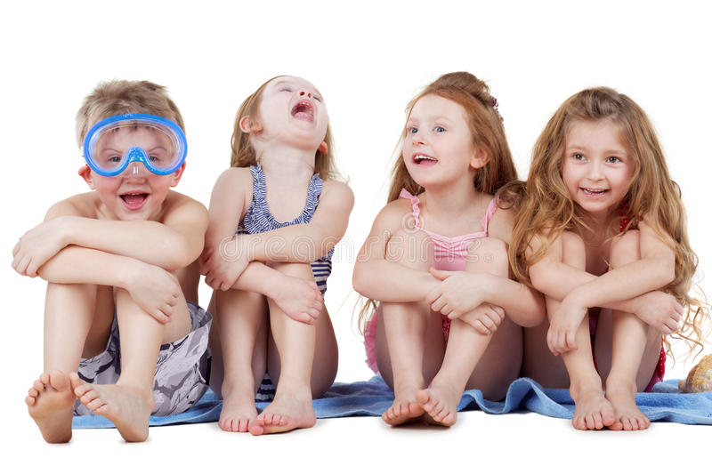 Boy in diving mask and three girls sit on towel