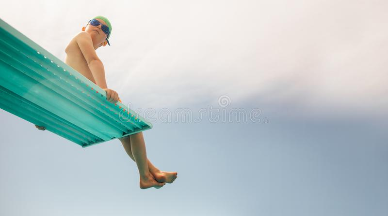 Boy on diving platform. Low angle view of boy in swim goggles and swimming cap sitting on diving board against bright sky. Boy on diving platform at pool royalty free stock photo