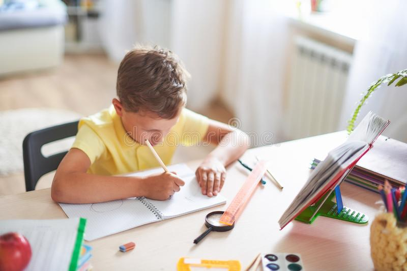 The boy does his homework at home. happy child at the table with school supplies concentrated writing in the retreat, doing stock image
