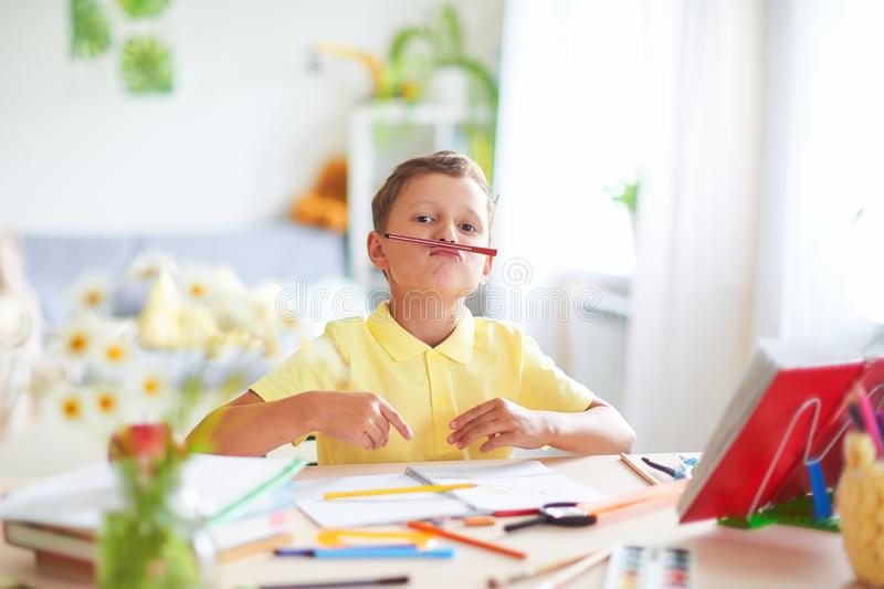 The boy does his homework at home. happy child at the table with school supplies funny smiles and wrinkles nose royalty free stock photos