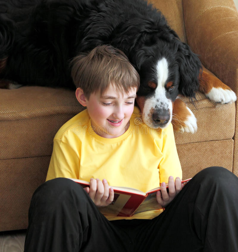 Boy with dog. The boy is sitting on the floor and reading a book, a dog spies